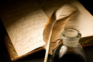 Old book with feather and inkpot