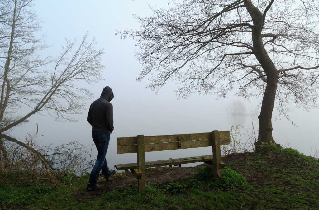 Man aproaching a bench at a lake on a foggy day.